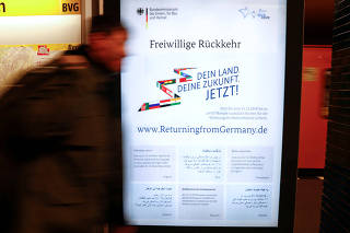 A man walks beside a poster advertising financial help to refugees who want to return to their home countries issued by Germany's Interior Ministry, at a metro station in Berlin