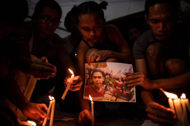A espera da decisão do tribunal, manifestantes seguram fotos com Kian delos Santos (o adolescente morto) em frente ao local onde os policiais estavam detidos