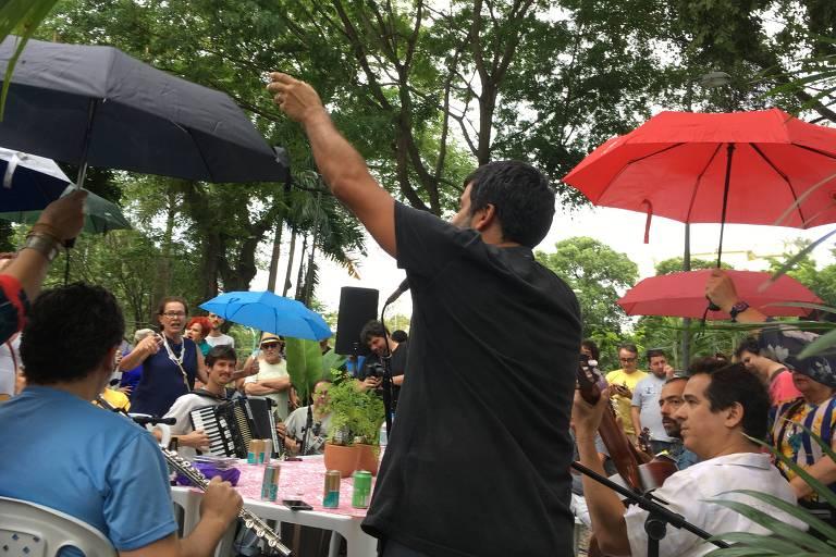 De costas, em primeiro plano, o cantor Pedro Miranda, no evento Choro na Rua  na praça do Jóquei, no Rio