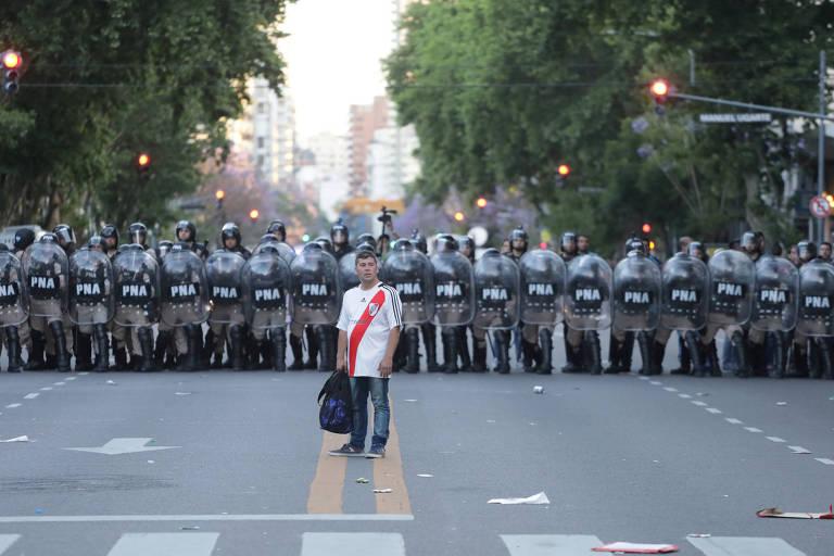 Torcedor do River Plate em frente a cordão de policiais antes da partida adiada em Buenos Aires no último sábado