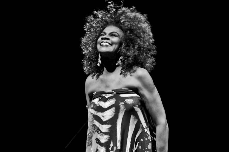 Imagem em preto e branco. A cantora Zezé Motta está no centro da imagem, ela dá um grande sorriso, olhando para o alto. Seu vestido é de estampas e tomara-que-caia.