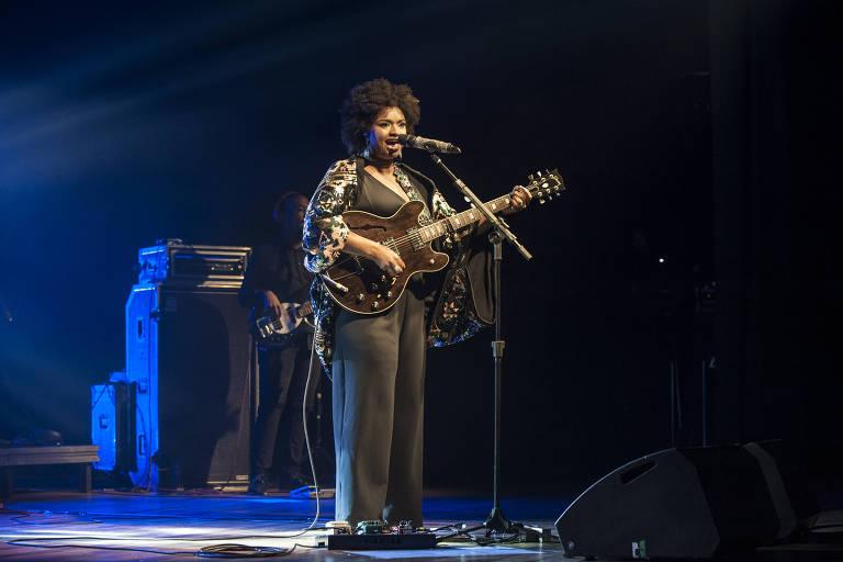 Vestida de preto, cantora Ellen Oléria canta e toca guitarra em show