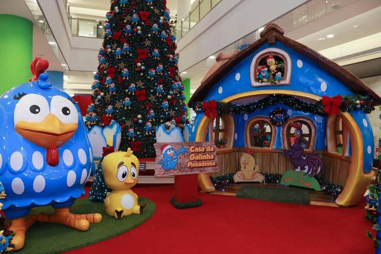 Galinha Pintadinha (de azul, com franjas brancas), de pé, e Pintinho Amarelinho, sentado, em espaço do shopping para as crianças brincarem. Ao lado deles, a Casa da Galinha Pintadinha e, ao fundo, uma árvore de Natal repleta de miniaturas da Galinha Pintadinha