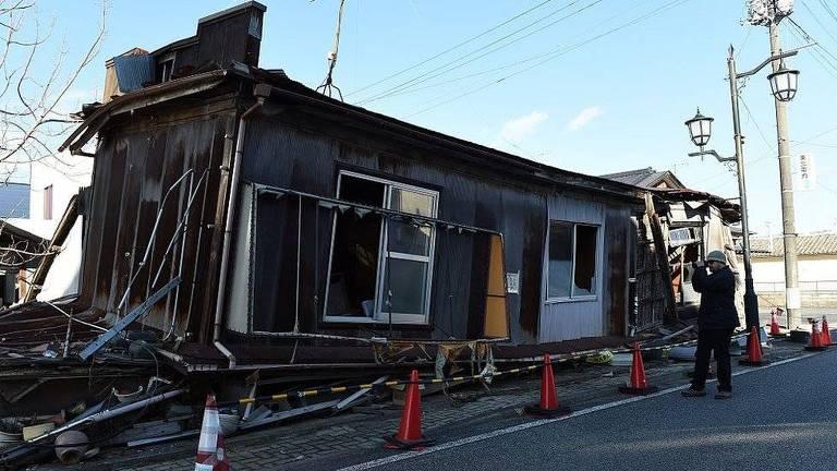 Em Fukushima, no Japão, onde o tsunami provocou a morte de 19 mil pessoas, os turistas tiram fotos na frente de casas destruídas
