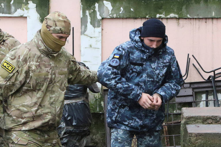 A member of Russia's FSB security service escorts a detained Ukrainian navy sailor before a court hearing in Simferopol
