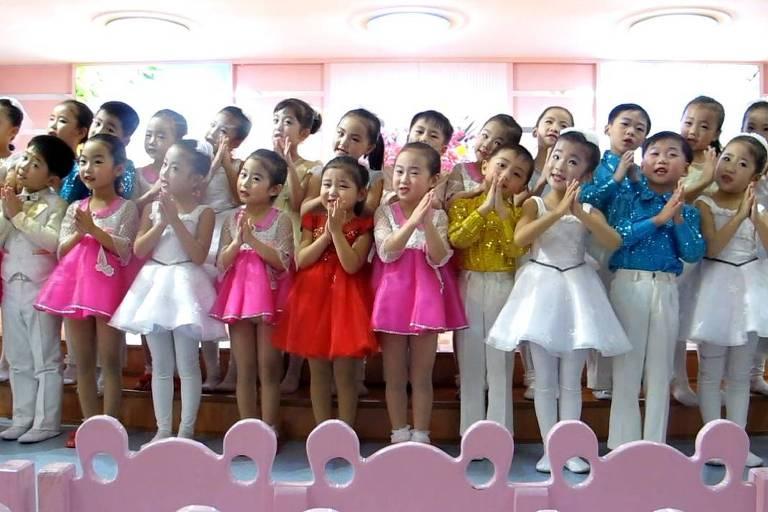 Meninos e meninas em roupas de apresentação batem palma e cantam música