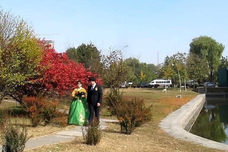 Noiva com traje tradicional coreano de saia longa verde claro e blusa amarela e noivo de terno preto posam para foto em jardim da hospedaria Ansan, em Pyongyang