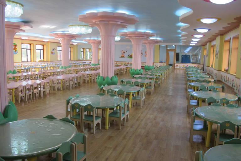 Salão com fileiras de mesas circulares com tampo verde e mesas retangulares com tampo rosa, de altura baixa, para crianças