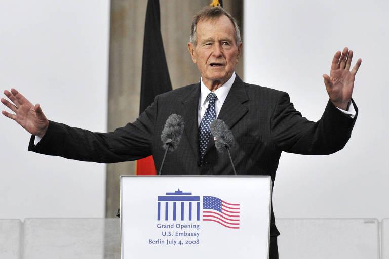 Em um palanque com braços levantados, o ex-presidente George Herbert Walker Bush faz um discurso durante evento na Alemanha