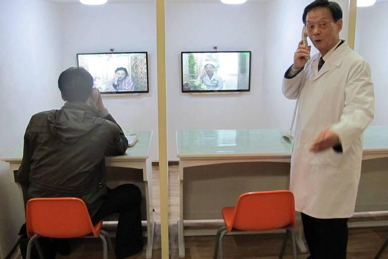 homem sentado em cadeira laranja fala por telefone com mulher, cuja imagem aparece num monitor; ao lado, funcionário do hospital conversa com enfermeira, cuja imagem também aparece no monitor