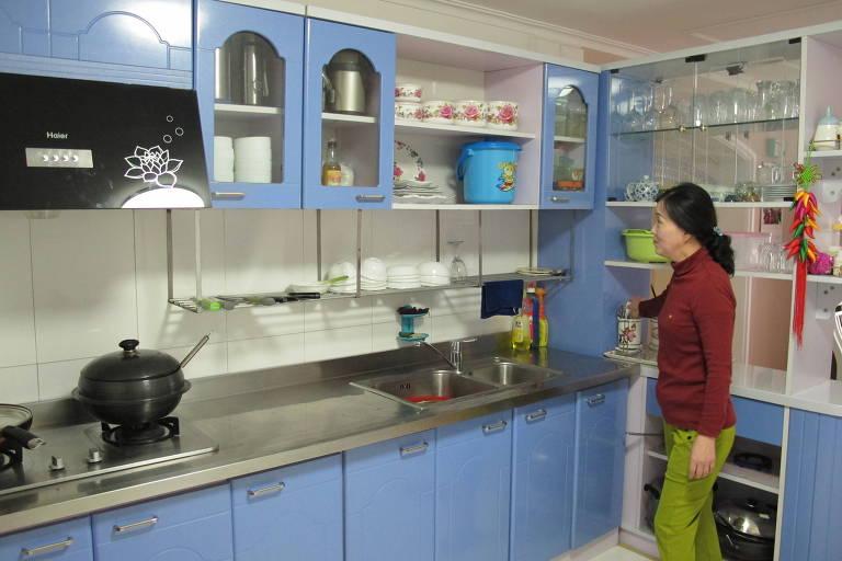 A aposentada Ro Kyong Ae, 54, na cozinha do apartamento que ela e o marido receberam do Estado