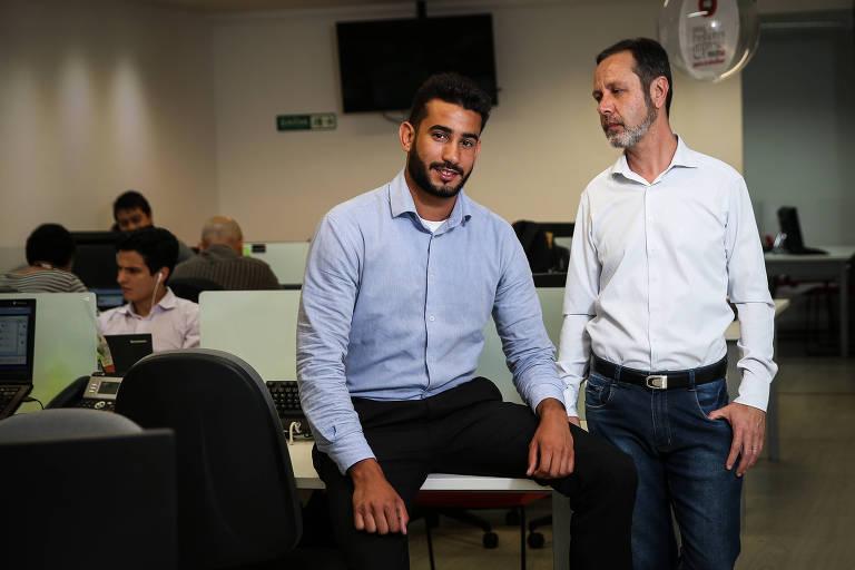 William Almeida e Wladimir Ramalho lado a lado no escritório onde trabalham