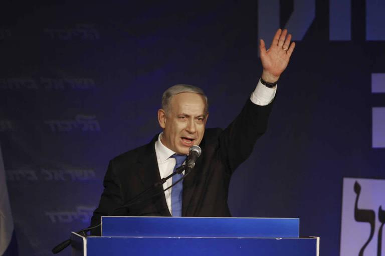 Em uma tribuna, de paletó e com braço levantado,  o premiê de Israel, Binyamin Netanyahu, saúda apoiadores na capital, Tel Aviv