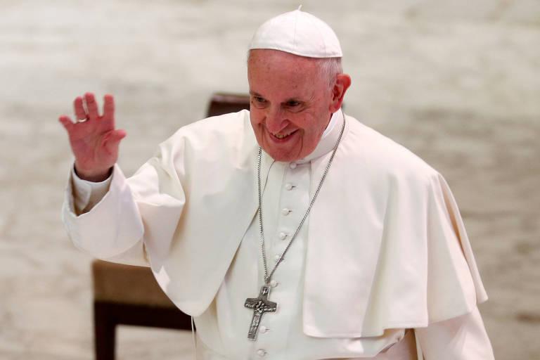 Com vestes brancas e usando uma cruz, papa Francisco faz um aceno com o braço