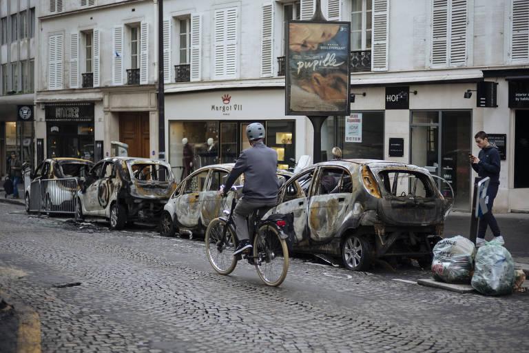 Ciclista passa em rua de Paris neste domingo ao lado de carros queimados em protesto no sábado