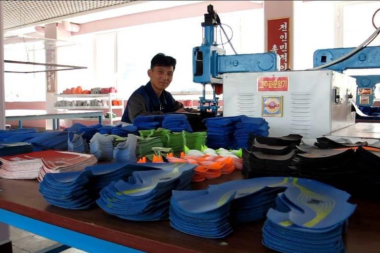Operário opera máquina com peças de tênis empilhadas à sua frente