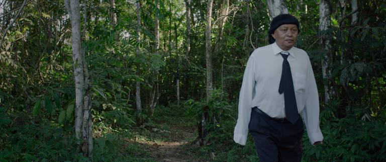Cena do filme 'Ex-Pajé'; seu protagonista, Perpera Suruí, ex-pajé de sua aldeia, está com coronavírus; vemos um homem com o cabelo cortado à moda indígena, porém com camisa branca, calça e gravata pretas, andando na floresta