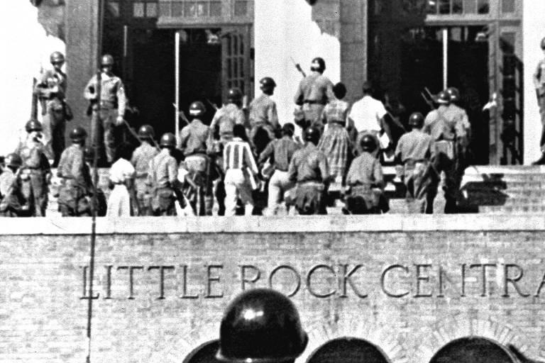 Policiais escoltam alunos negros em Little Rock, no Arkansas, após o governo local usar agente para impedir a entrada dos estudantes em 1957
