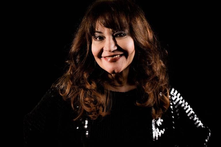 Cantora Claudya posa com roupa preta e detalhes em branco diante de parede preta