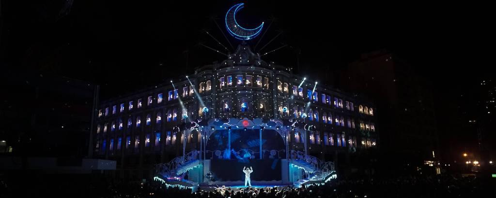 Ator em palco com prédio iluminado ao fundo