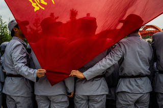 Aerospace workers, wearing Long March-style uniforms, hold a flag in Yan'an in the Shaanxi province of China.