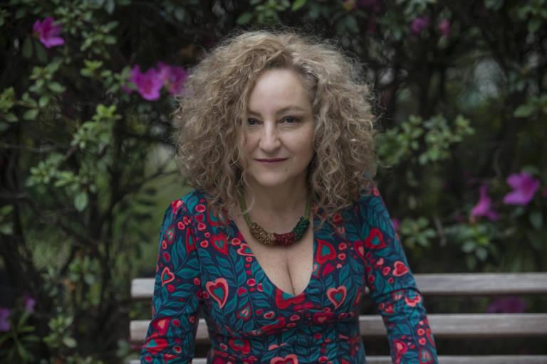 Com vestido decotado nas cores verde e vermelho, a cantora Anaí Rosa posa para foto. Ela é loira e tem cabelo cacheado