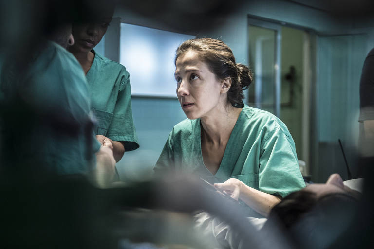 Carolina (Marjorie Estiano) atende Mara (Elisa Pinheiro), que sofreu sérias lesões ao retirar da mão do filho um rojão prestes a explodir, colocado à força pelo marido. Ao pegar o objeto, que explode em seguida, ela fica com parte da mão e um dedo comprometidos