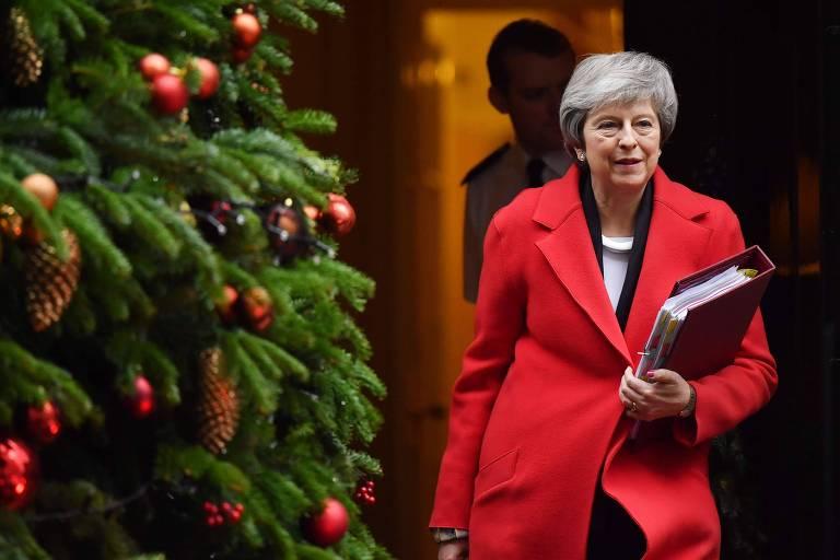 A primeira-ministra Theresa May deixa a residência oficial de Downing Street 10 em Londres para participar de sessão no Parlamento nesta quarta (5)