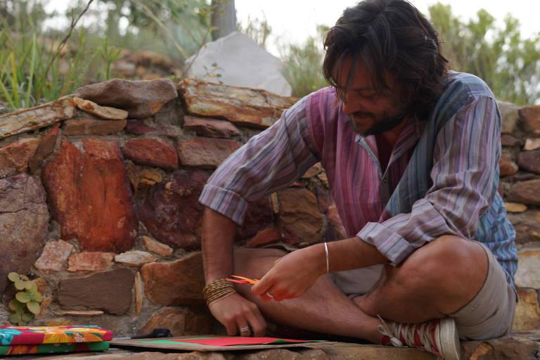 Homem barbado com cabelo grande usa papéis coloridos e tecidos para fabricar caderno