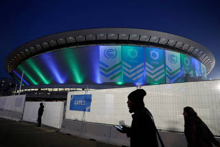 People walk in front of the venue of the COP24 U.N. Climate Change Conference 2018 in Katowice