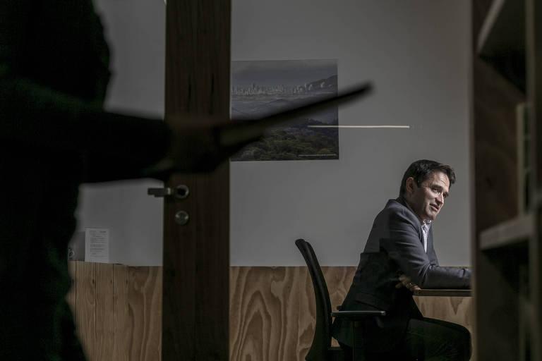 Justin Adams, novo diretor da TFA 2020 (aliança pelas florestas tropicais 2020), sentado em cadeira atrás de um vidro; há sombras em volta