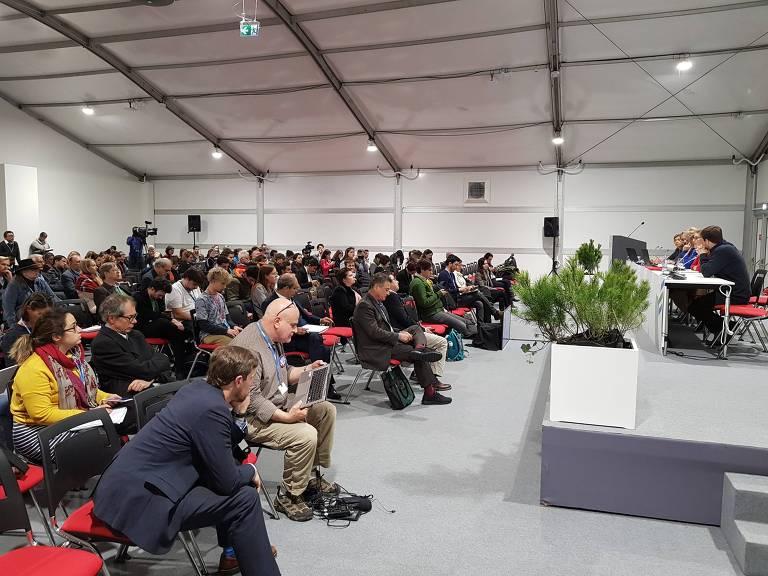 Reunião com dezenas de pessoas assistindo a uma discussão