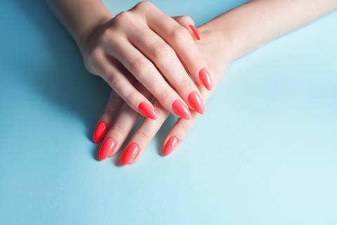 Women's hands with perfect red manicure. Nail Polish red coral color. blue background, close-up
