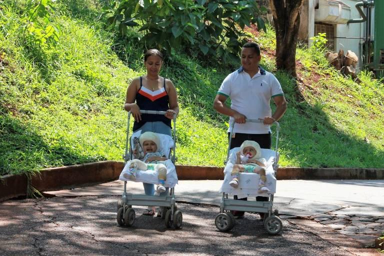 Pais levam as filhas para passear em carrinhos