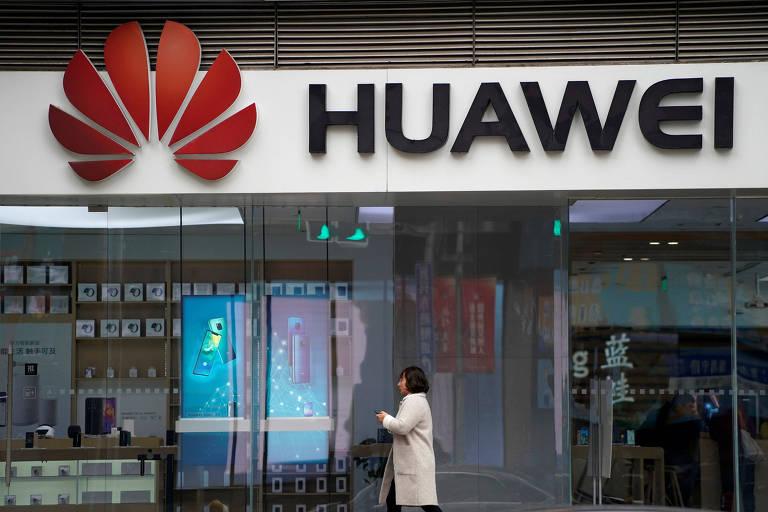 Mulher em frente a logo da Huawei em Xangai, na China; gigante asiática está sob escrutínio dos EUA e de aliados