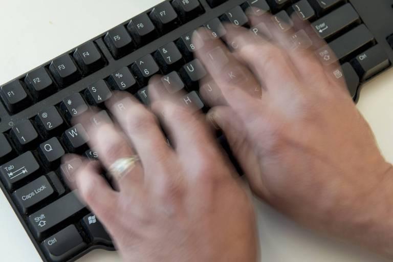 homem digita em teclado de computador