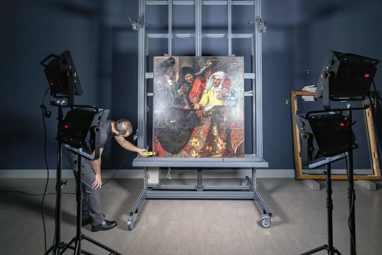 Quadro está montado em cavalete, homem ajusta grandes lâmpadas que iluminam a imagem