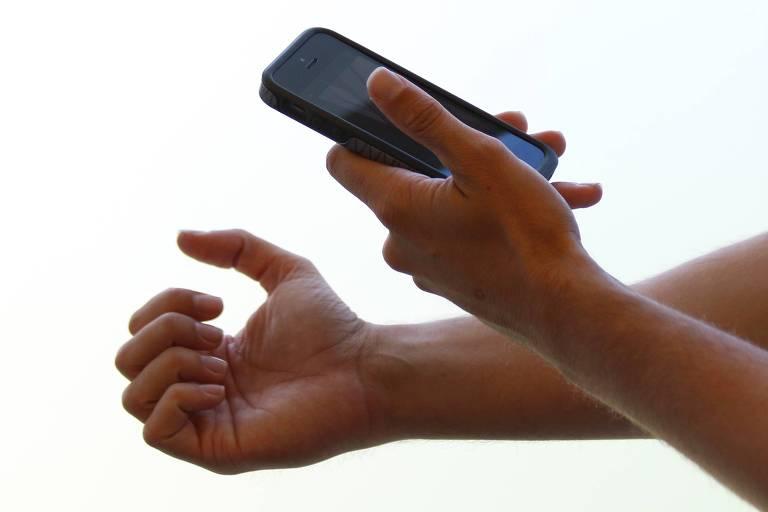 Pessoa fotografa unhas com celular