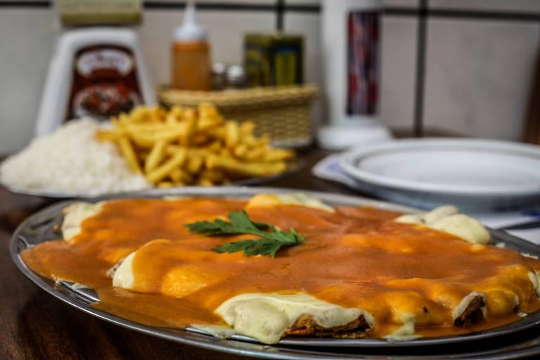 Coberto com generosas camadas de queijo e molho, o bife à parmigiana do Jhony's é o carro chefe da casa