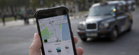 FILE PHOTO: A photo illustration shows the Uber app on a mobile telephone, as it is held up for a posed photograph, with a London Taxi in the background, in London, Britain November 10, 2017.  REUTERS/Simon Dawson/File Photo ORG XMIT: SJW001