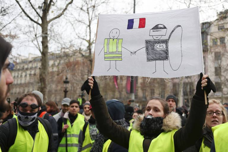 """Manifestante segura cartaz em Paris que mostra união dos """"coletes amarelos"""" com as força policiais, no quarto final de semana de protestos na França"""