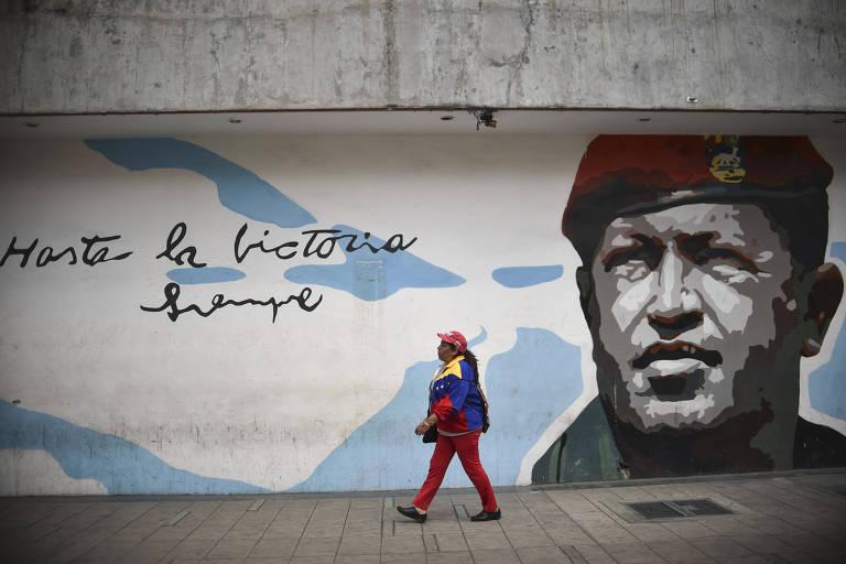 Apoiadora do chavismo passa em frente a muro com pintura de Chávez em Caracas