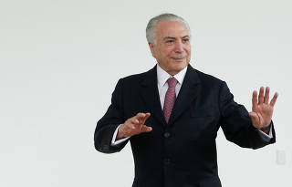Brazil's President Michel Temer gestures after a breakfast with foreign media at Alvorada Palace in Brasilia