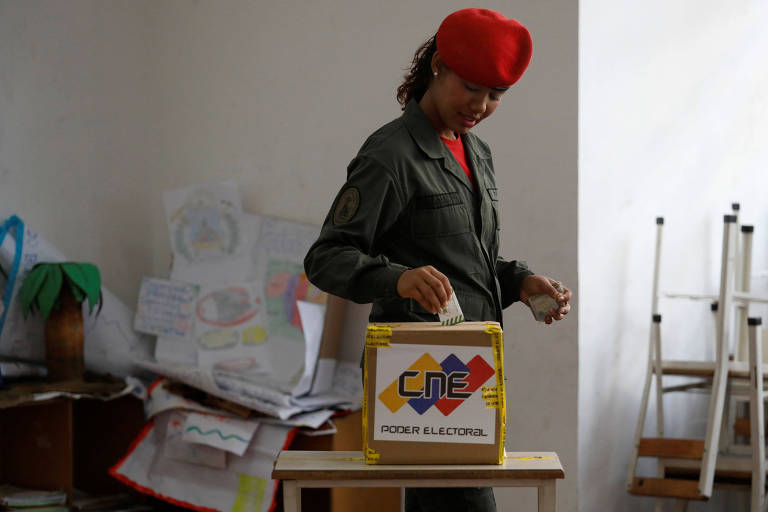 A Venezuelan soldier casts her vote at a polling station during the municipal legislators election in Caracas