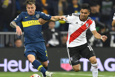 Boca Juniors' Julio Buffarini (L) and River Plate's Gonzalo Martinez vie for the ball during the second leg match of their all-Argentine Copa Libertadores final, at the Santiago Bernabeu stadium in Madrid, on December 9, 2018. (Photo by Gabriel BOUYS / AFP)