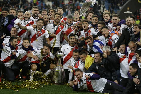 Argentina's River Plate players pose with the trophy as they celebrate their victory in the Copa Libertadores final soccer match at the Santiago Bernabeu stadium in Madrid, Spain, Monday, Dec. 10, 2018. (AP Photo/Thanassis Stavrakis) ORG XMIT: XTS162