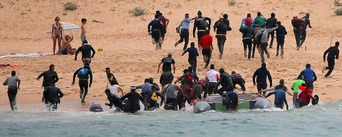 REFILE - REMOVING MIGRANTS' NATIONALITY Migrants disembark from a dinghy at