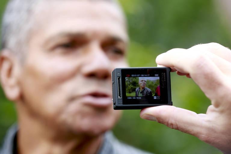 Pedro no fundo, desfocado, com câmera que o grava no primeiro plano