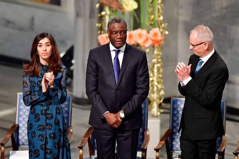 A ativista iraquiana Nadia Murad com o ginecologista congolês Denis Mukwege (centro) e o membro do comitê do Nobel Henrik Syse durante a cerimônia de entrega do prêmio em Oslo