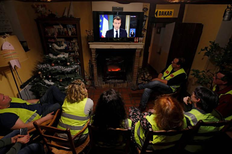 Manifestantes vestindo coletes amarelos, sentados diante de uma televisão, assistem ao pronunciamento